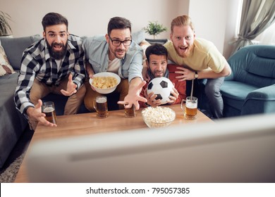 Young football fans are drinking beer,cheering and smiling while watching football game at home.