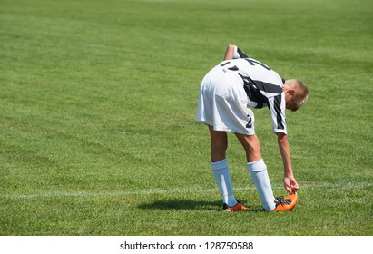 young football player doing stretching exercises