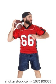 A young football player standing in his uniform and a beard ready to
