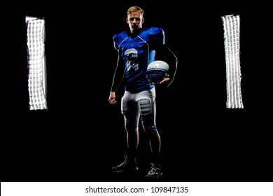 A young football player stands in front of the lights in his uniform holding his helmet.