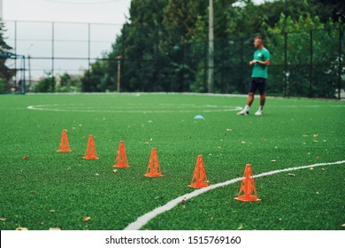 Young football player stands on the green soccer field. Orange cones on the grass.