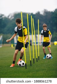 Young Football Players Running Slalom and Dribbling With Balls Between Training Poles. Soccer Practice for Teenage Boys. Junior Level Soccer Team Traing Unit