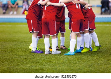 Young football soccer players in red sportswear. Young sports team on pitch. Pep talk before the final match. Soccer school tournament. Children on sports field.