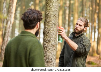 Young forester marks a tree with red paint from spray can for the wood harvest