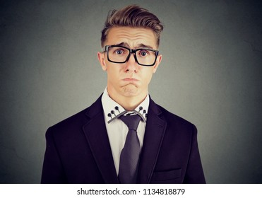 Young formal man in suit and glasses looking insulted and pity frowning face and crying on gray background