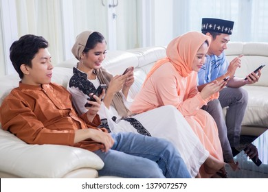 Young four Muslim people using a mobile phone while sitting on the sofa in the living room at home