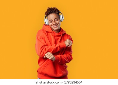 Young freckled african american man wearing red hoodie and headphones standing isolated on yellow background listening to music dancing smiling cheerful
