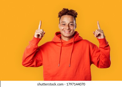 Young freckled african american man wearing red hoodie standing isolated on yellow background pointing up at copy space for text or product smiling cheerful