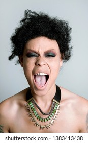 Young freckled mixed race woman with short curly hair makes a fierce open mouthed screaming face. Close up beauty photo of a frustrated or angry female model wearing a green and gold choker necklace.