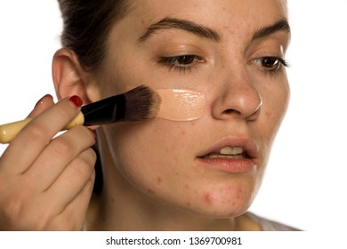 Young freckled woman applying liquid foundation on white background