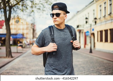 Young free beautiful fashionable hipster guy walking down the street, through the park, wearing a cap with a backpack, t-shirt, sunglasses, urban style, sport casual