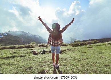 Young free inspired hipster woman traveler with open arms enjoys tranquillity and calmness while traveling to the mountains. Happy moments in life