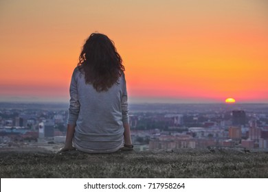 Young free woman sitting and looking at summer sunrise over the city. Thinking concept photo
