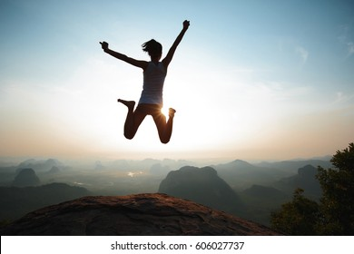 young freedom woman jumping on sunrise mountain top