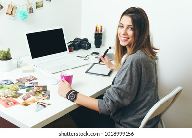 Young freelance female photographer at home, working on laptop in home office