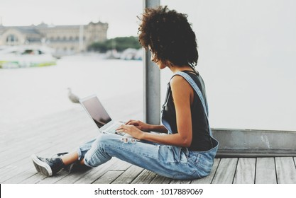 a young freelance girl is creating the design of a new web site while sitting on a wooden embankment. black-skinned female student uses laptop computer for studying on online courses using public WiFi