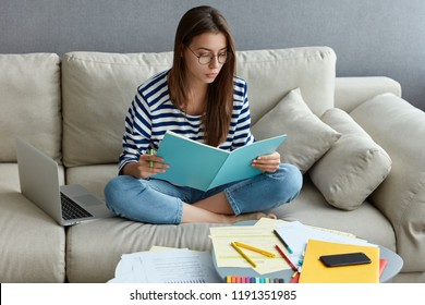 Young freelancer does ditance job at home, studies literature, learns foreign language in internet, writes down unknown words, sits crossed legs on couch, spends time at home, connected to wifi