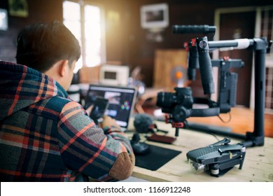 Young freelancer man editing video on laptop and checking smartphone for uploading video to internet online or social media.