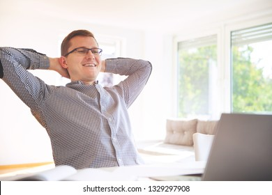 Young freelancer in white working with laptop at home