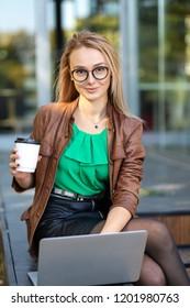 Young freelancer woman with glasses using laptop and drinking coffeee while sitting on porch of house