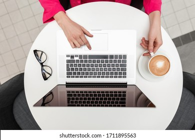 Young freelancer woman leads personal blog on the Internet. Business girl working on modern laptop and drinks coffee. Top view close-up on white desktop on which there is coffee,laptop,fashion glasses