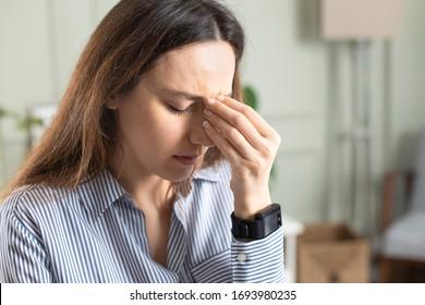Junge freiberufliche Frau mit Kopfschmerzen im Heim