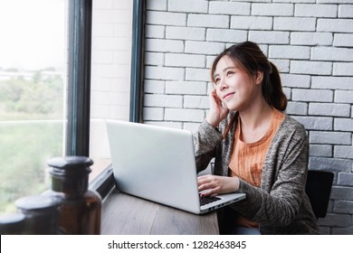 Young Freelancer Woman Working on Computer Laptop in Cozy House, Female in Thoughtful Posture Looking Outside Window, Lifestyle of New Generation People, Dreaming for Success