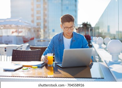 Young freelancer working on laptop outdoors