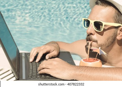 Young freelancer working on vacation next to the swimming pool