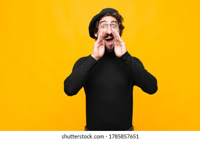 young french artist man feeling happy, excited and positive, giving a big shout out with hands next to mouth, calling out against orange wall