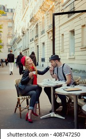 Young french couple have a romantic date in a Parisian street cafe