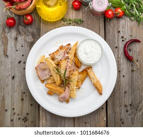 Young fried potatoes with bacon and onions, on a wooden table