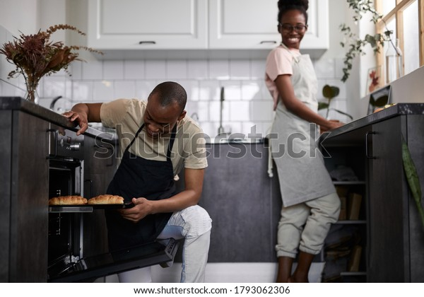 young friendly african couple is cooking together in the kitchen, man and woman happy to prepare meal as one team.