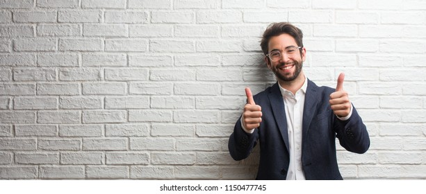 Young friendly business man cheerful and excited, smiling and raising her thumb up, concept of success and approval, ok gesture