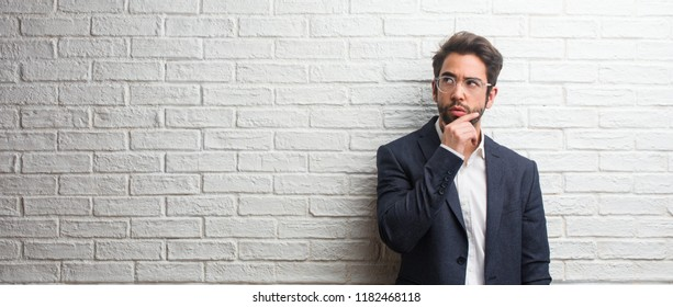 Young friendly business man doubting and confused, thinking of an idea or worried about something