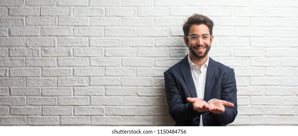 Young friendly business man holding something with hands, showing a product, smiling and cheerful, offering an imaginary object