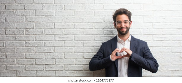 Young friendly business man making a heart with hands, expressing the concept of love and friendship, happy and smiling