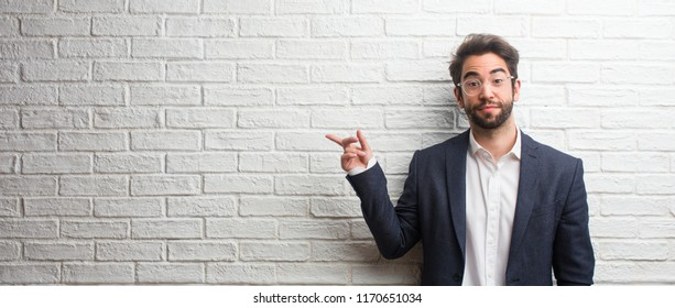 Young friendly business man pointing to the side, smiling surprised presenting something, natural and casual