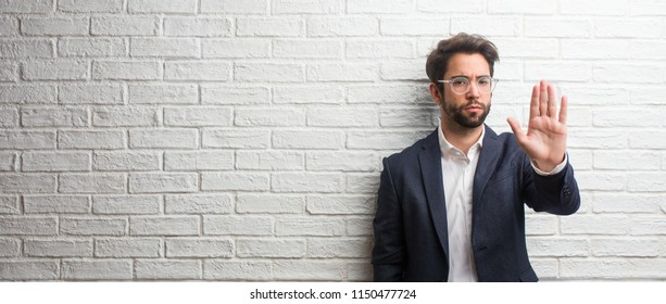 Young friendly business man serious and determined, putting hand in front, stop gesture, deny concept