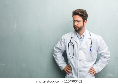 Young friendly doctor man against a grunge wall with a copy space very angry and upset, very tense, screaming furious, negative and crazy
