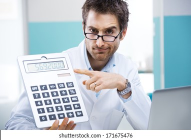 Young friendly doctor pointing at a big calculator.