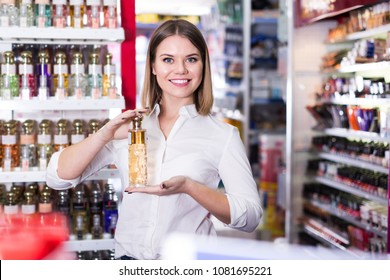 Young friendly female seller offering perfume at cosmetics shop