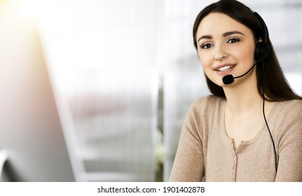 Young friendly girl in headsets is talking to a firm's client, while sitting at the desk in sunny office. Call center operators at work