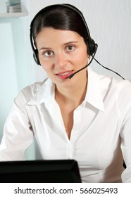 Young friendly operator with headset working at the office.