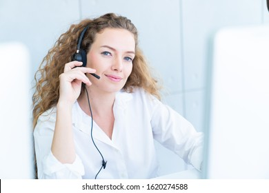 Young friendly operator woman agent with headsets working in a call centre,smile and hand touch at headphone concept for service mind in call center