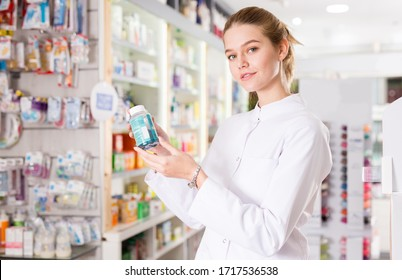 Young friendly pharmacist offering reliable medicine in pharmacy