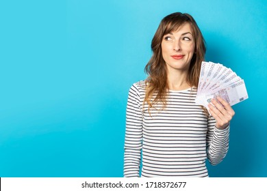 Young friendly woman in casual t-shirt holding money in her hands and looking to the side with an embarrassed face on isolated blue background. Concept of wealth, win, credit. Copy space