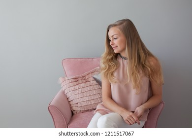 Young friendly woman sitting in a chair with a notebook in her hands. A nice companion. Light gray background, copy space