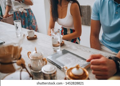 Young friends around the wooden table in coffee shop while drinking first class delicious coffee in a traditional manner