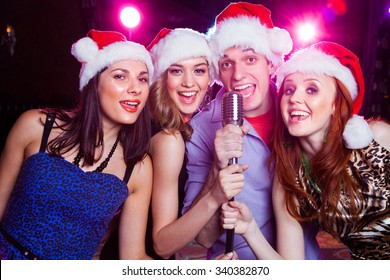 young friends in the bell Santa Claus sing karaoke microphone